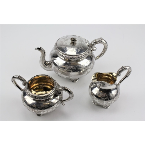 63 - A three piece silver Chinese tea set, floral engraved and decorated, with ivory insulating handles. ...