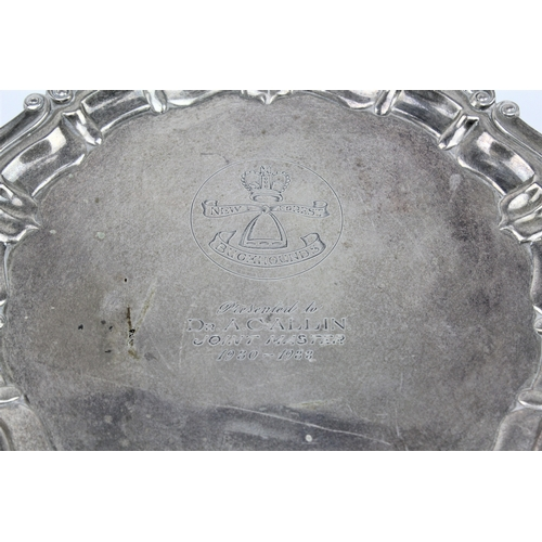 11 - A silver floral bordered waiter, resting on three legs, RE Porter, H mark, inscribed. 310 grams....