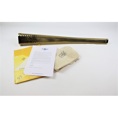 579 - A London 2012 Olympic torch, brass effect, pieced decoration, along with cloth carrying case and pap...