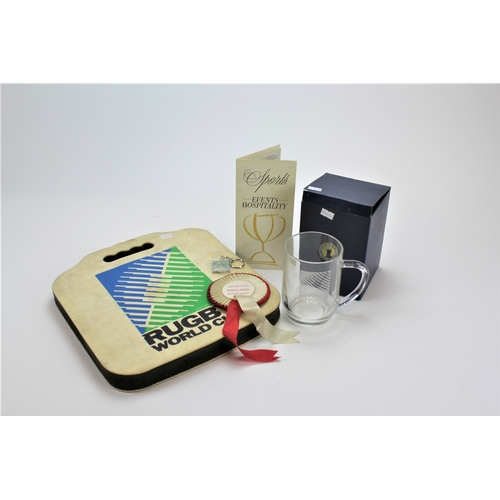 580 - A 1991 Rugby World Cup mug, medal, rosette, cushion, coach pass, and other related items....