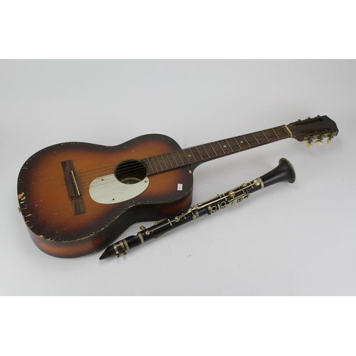 523 - An ebony cased clarinet, along with a guitar....