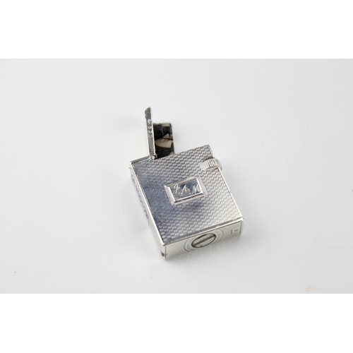 11 - A rare early silver cigarette lighter, by Alfred Dunhill, engine turned....