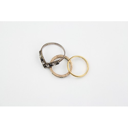 32 - A 22 carat gold wedding ring, 2.4 grams, along with an emerald eternity ring, and one other, and a b...