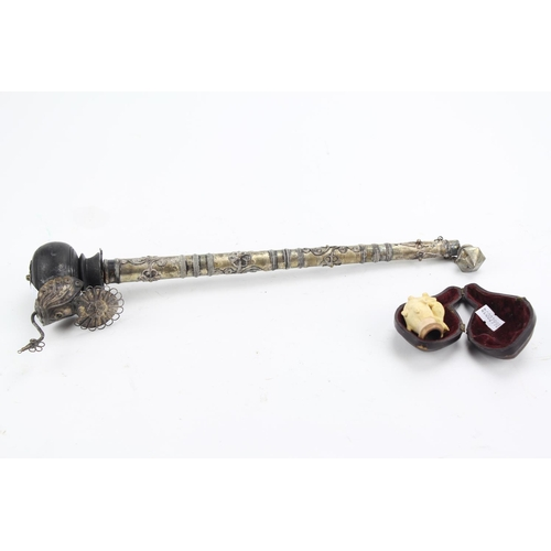 487 - An Asian white metal and wood opium pipe, depicting a stylised peacock and floral rope decoration, a...