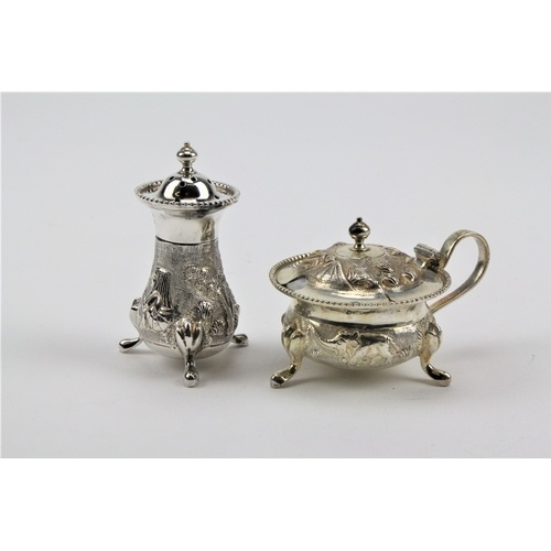 20 - A sterling silver Indian mustard pots, floral embossed & a silver pepper shaker....
