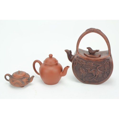250 - A Yixing ware tea pot of globular form and pulled handle. one other decorated with a dragon and a si...