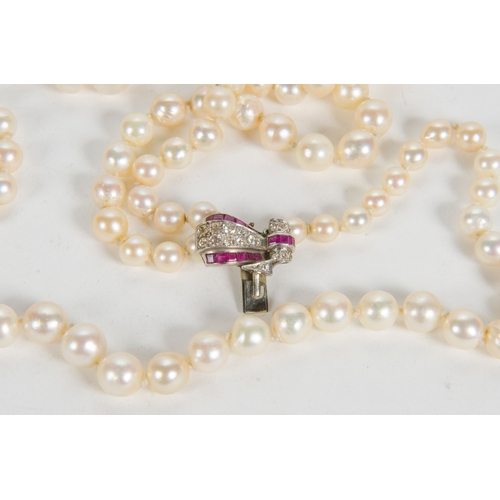 16 - An Art Deco three strand pearl necklace, with a diamond and ruby set clasp, platinum mounted....