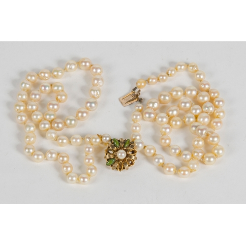 17 - A two strand cultured pearl necklace, with a 9 carat clasp, set with green stones....