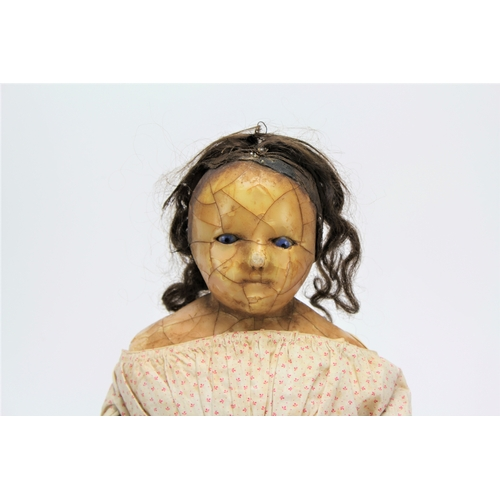 451 - A Victorian wax headed doll, with piercing blue eyes, decorated in a period dress, human hair, pleas...