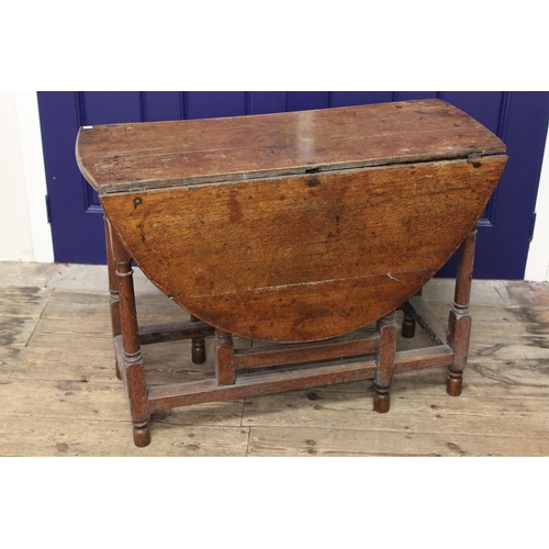 291 - An Antique oak drop flap table resting on turned legs. Measuring approximately across 40 inch x Heig...