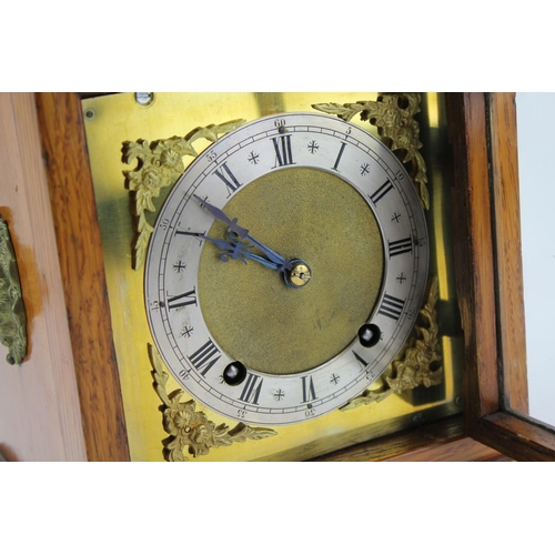 126 - An Oak cased bracket clock with a brass and steel chapter ring, decorated with lion handles and bras...