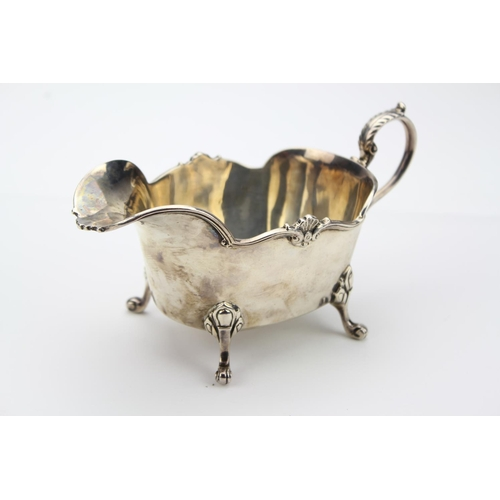38 - A Silver cast bordered Silver Sauce Boat, scroll handle and pad feet, Birmingham. E  190 grams....