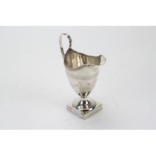 8 - A Georgian Silver Bright Cut and Engraved Helmet Shaped Cream Jug with Beaded Decoration....