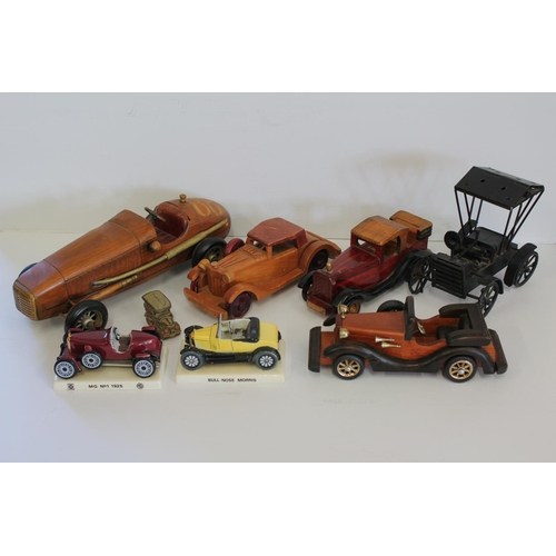 325 - A Collection of 7 model cars to include 4 in Wood, 2 in China on plinths & 1 Cast Iron.