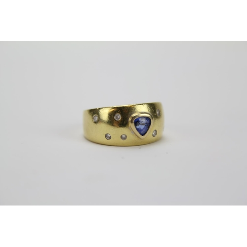 52 - A Ladies Triangular shaped Sapphire & 7 Diamond Ring, marked 750. Size M. Weighing: 8.3 grams....
