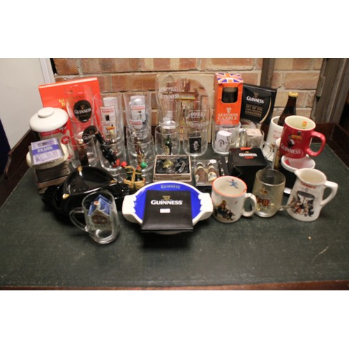 130 - A Collection of 50+ Guinness Memorabilia to include Glasses, Mugs, Ashtrays along with other boxed i...