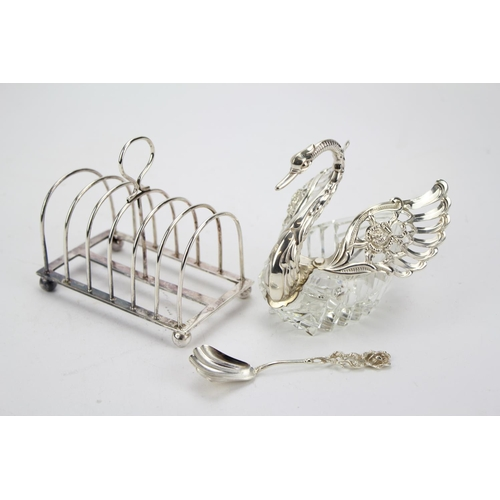 47 - A Silver 6 Bar Toast Rack. London g. Weighing 118g. Along with a 835 marked Swan Ornament....