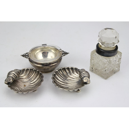 12 - An Art Nouveau silver salt cellar with loop handles, a cut glass cologne bottle and a pair of shell ...