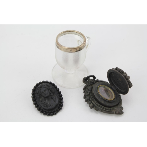 41 - A Victorian 'Jet' carved memorial locket along with a similar brooch & a silver mounted tot holder.