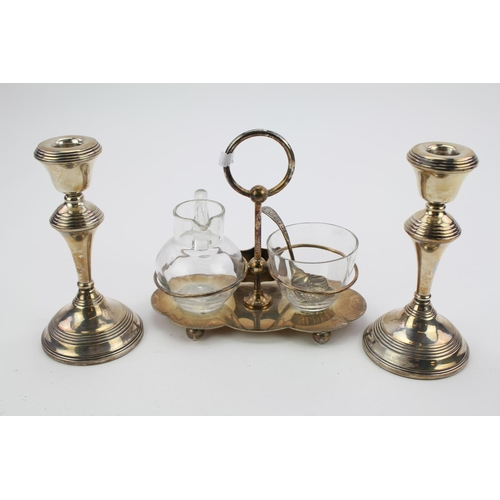 6 - A pair of stamped silver candlesticks and a Silver plated sugar and cream holder.