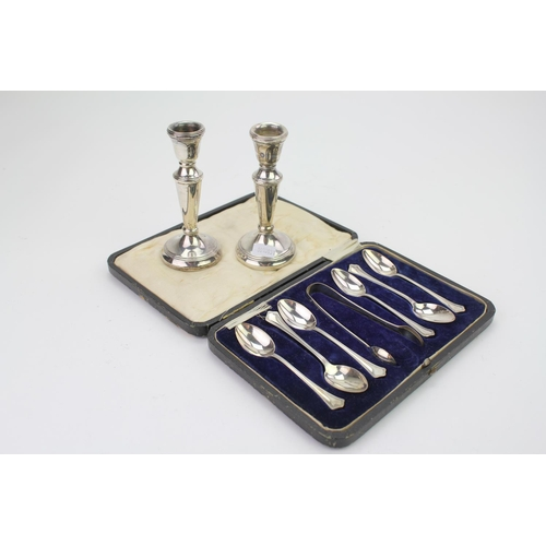2 - A set of 6 Silver tea spoons and tongs in case along with a pair of Silver covered candlesticks.
