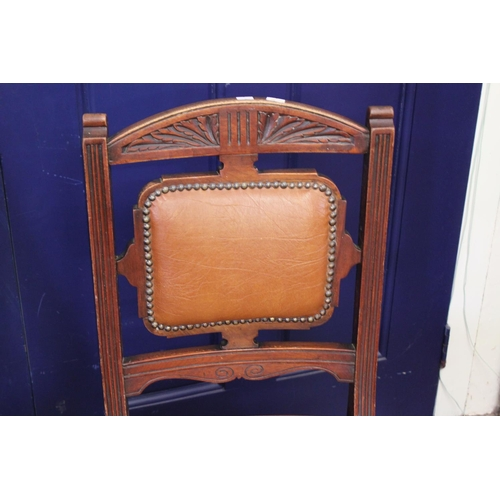 320 - A Pair of Edwardian Carved Leather Seated Dining Chairs resting on Turned Legs with Front Castors.