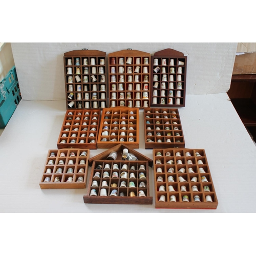 417 - A large Collection of Thimbles contained in wooden shelving units as pictured.