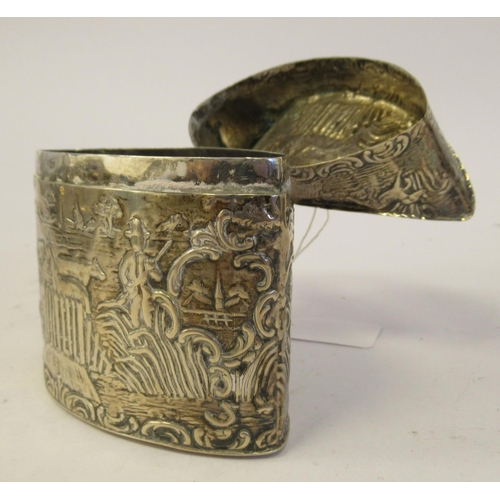 13 - A Dutch silver coloured metal oval tea caddy, having straight sides, a concave, outset hinged lid an...