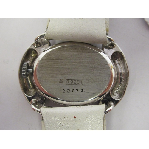 35 - A lady's Bucherer silver coloured metal/stainless steel cased wristwatch, faced by an oval Roman dia...