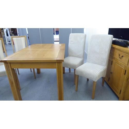 31 - A modern light oak dining table, raised on block legs 30