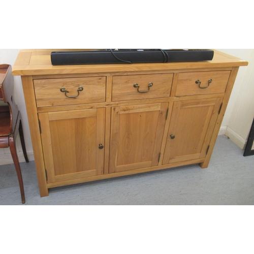 33 - A modern light oak sideboard with three drawers and three cupboard doors, raised on block legs 33
