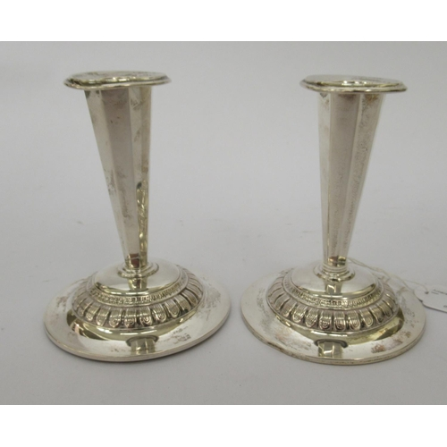 7 - A pair of Continental silver coloured metal candlesticks with tapered octagonal stems, on loaded cir...