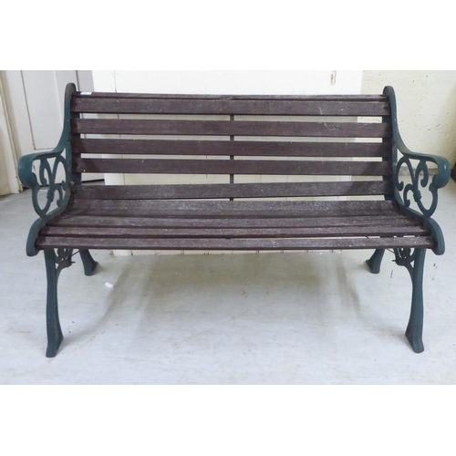 11 - A Victorian style slatted teak bench with C-scrolled cast iron supports 50