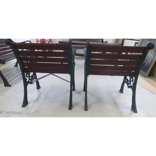 12 - A pair of Victorian style slatted teak terrace armchairs with C-scrolled cast iron supports