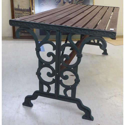 16 - A Victorian style slatted teak terrace table with C-scrolled cast iron supports 26
