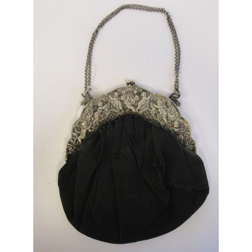 26 - An early 20thC white metal framed black satin evening bag with cherubic, latticed and scrolled ornam...