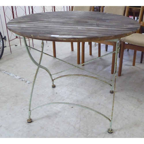 34 - A slatted teak terrace table, raised on a folding, painted cast iron crossover underframe 30