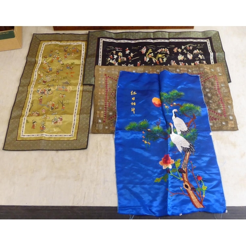 41 - One framed and four loose 20thC Oriental textiles: to include a blue silk unframed panel of cranes o...