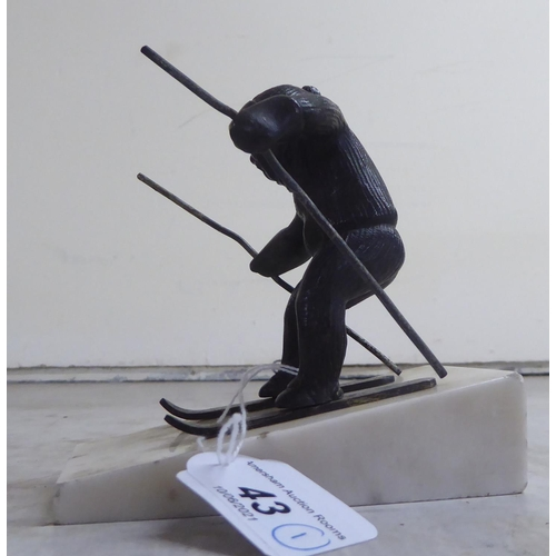43 - A mid 20thC cast bronze model, a skier, on a sloping marble plinth 4.75