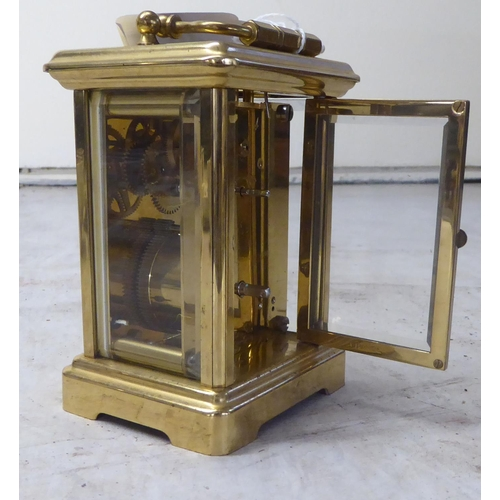 46 - A modern lacquered brass carriage timepiece with bevelled panels and a folding top handle; the movem...