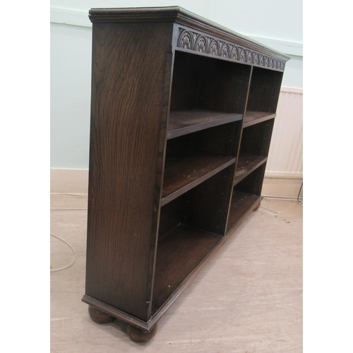 12 - A mid 20thC Old English style oak open front bookcase with four height adjustable shelves, on a plin...