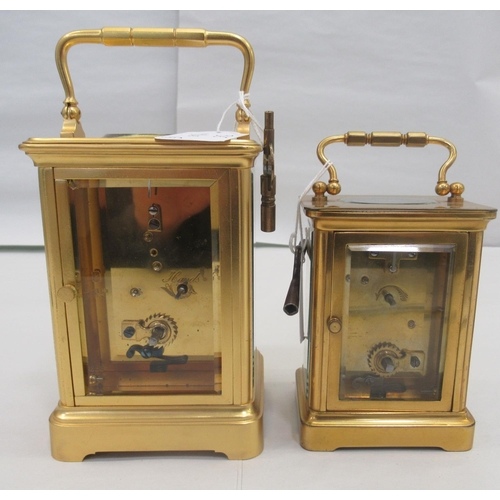 36 - Two similar 20thC brass cased carriage timepieces with bevelled glass panels and folding top handles...