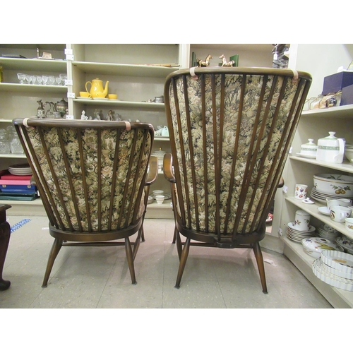 48 - An Ercol dark stained beech and elm framed high spindled back, open arm chair; and a matching lower ...