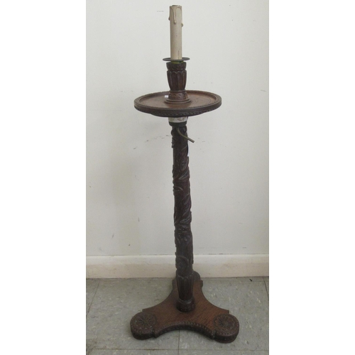 21 - An early 19thC profusely foliate and rosette carved candlestand with a dished top and column, raised...