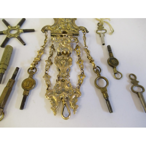 39 - A decoratively cast gilt metal chatelaine style belt clip, the chain pendant with provision for watc...