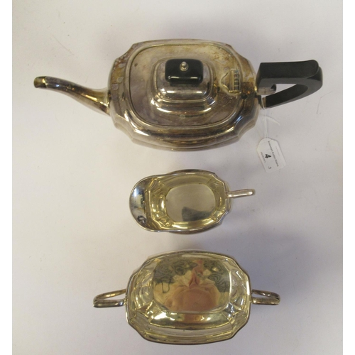 4 - A three piece silver tea set of elongated, bulbous, panelled form with incurved corners, on bun feet...