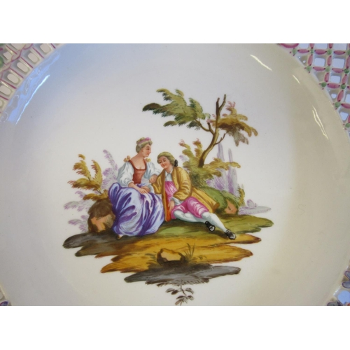 45 - A pair of 20thC Meissen porcelain plates, each featuring a couple in a garden setting with a wide, w...