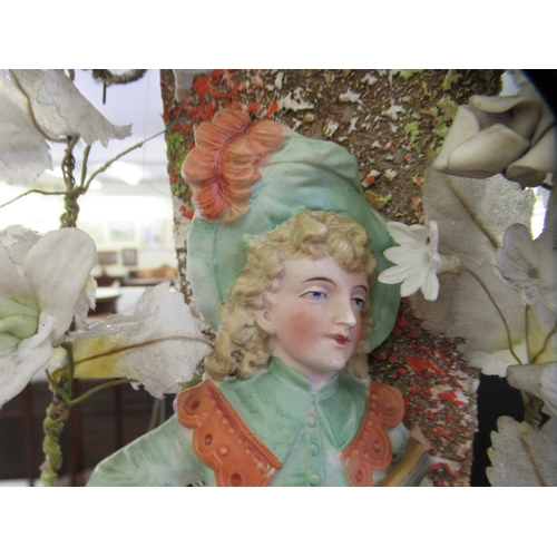 40 - A late 19thC Continental display, porcelain figures beneath an arbour of porcelain and silk flowers...