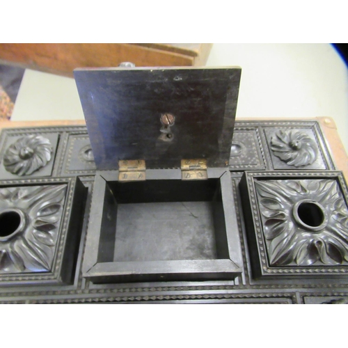 15 - A late 19thC carved ebony desktop writing box, featuring twin ink bottle holders, separated by a cen...