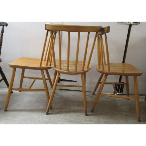 58 - A set of three mid 20thC Ercol beech framed, spindled, level, curved back dining chairs, the solid s...